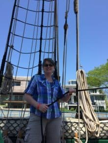 A woman in a plaid shirt holds a line on tall ship Friends Good Will